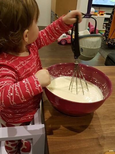 Dieťatko varí za kuchynskou linkou
