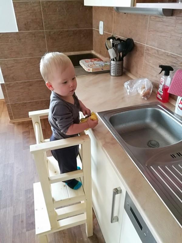 Dieťa stojí na učiacej veži pri dresea umýva riad